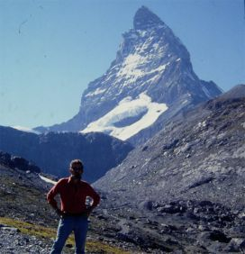 Muska Mosston standing at the base of a mountain peak