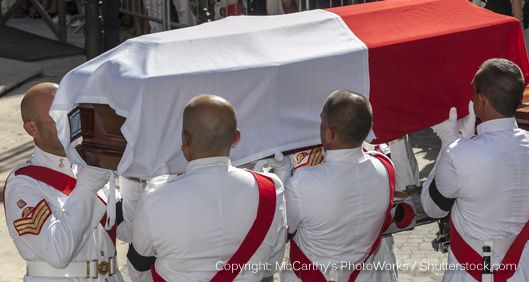 men in uniform carrying a coffin